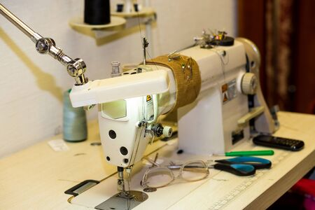 Sewing Process, Antique Sewing Machine with sewer, Lowkey lighting, factory shop. Closes making atelier with several sewing machines. Tailoring industry, fashion designer workshop, industry concept.cu