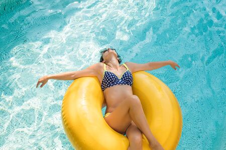 Young beautiful woman is relaxing in swimming pool with rubber ring.Pretty girl in swimwear is lying with closed eyes on the swim ring and smiling while swimming in the pool.Vacation,Wellness. Recreation concept