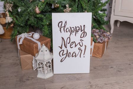 creative Happy New Year greeting card. Hand drawn text, Christmas tree with unique lettering hipster poster. Golden garland.Festive background in scandinavian design.Christmas tree with hanging on branches Wooden ornaments