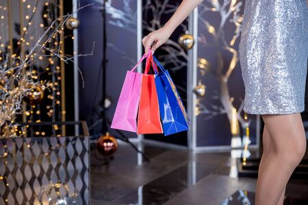 Christmas Shopping. Elegant woman in silver dress In Shopping Mall. Shopping Bags. Holidays and New Year Sales.Woman holding shopping bags making gift in christmas time. Big sale. Marketing and advertisement concept