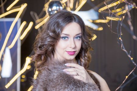 Rich celebrating woman wearing fur coat on blur festive background. Stylish positive pretty young woman having fun, wearing evening sparkling cocktail outfit and fur trendy coat, enjoying winter holidays party. Party mood. Фото со стока