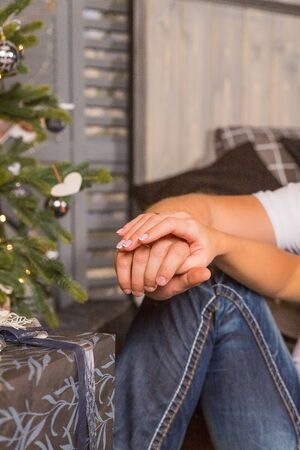 Close up of young couples hands caught together placing them on the knee.Man and woman with hands clasped over the knee during a date on new year. Happy moments together. Dating and romantic relationship concept.