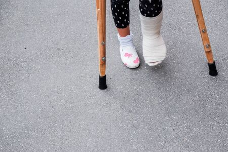 Little girl with crutches at the stair. Back to school Stockfoto