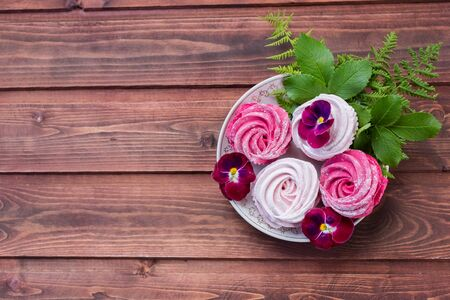 Céfiro colorido sobre fondo de madera. Conjunto de céfiro blanco y rosa casero o malvavisco sobre fondo de madera. Malvavisco, merengue, céfiro, pansy. Sabrosos merengues. Copiar espacio