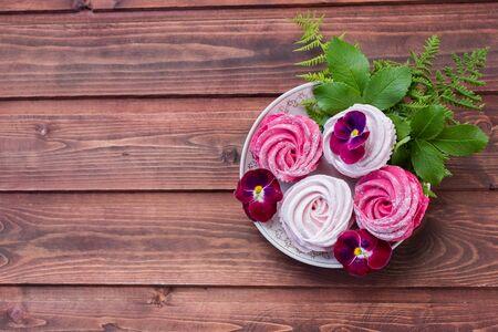 Zefiro colorato su fondo di legno. Set di zefiro bianco e rosa fatto in casa o marshmallow su fondo di legno. Marshmallow, Meringa, Zephyr, Pansy.Meringhe gustose.Copia spazio