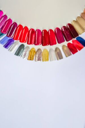 Nail polish in different fashion colors.Manicure cabinet, gel nail polish in a beauty salon for a girl. Set of different nail polish colours on palette in cosmetic store on white background, like rainbow. Copy space Imagens