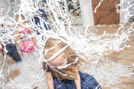Moscow,Russia ,June, 6, 2019: Paper show at the party. Paper party. Children playing with paper at birthday party.toddler smiles laughs lies in a huge pile of white confetti. Animation, birthday party,fun game, show scenery. Редакционное