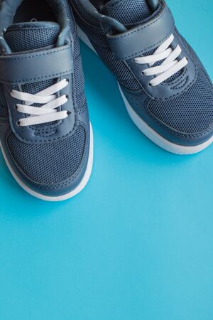 kids athletic shoes isolated on blue background.Pair of casual shoes on color background.Sneakers are shoes primarily designed for sports or other forms of physical exercise.Blue shoes.Copy space