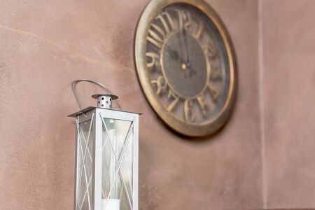 interior of the room in the style of steampunk, lantern,iron details. Antique Clock Isolated on beige Wall Background. Vintage Retro Clock, Decorative Old Fashioned Interior Design Element. loft style Zdjęcie Seryjne