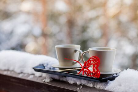 two cups with hot coffee or tea along with hearts on the background of the winter forest. decorations for Valentines Day or wedding. frosty sunny day on Valentines Day. Holiday greetings. Фото со стока
