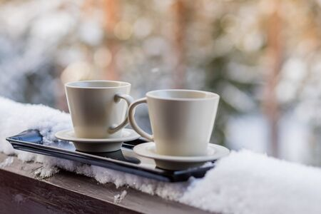 Steaming hot coffee in two mugs, buried in snow, on a balcony, on a bright winter morning. Breakfast for two. Cozy winter concept.Morning chill out on the fresh air,cup of tasty coffee.Winter still life