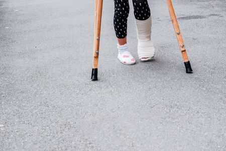 child using crutches and broken legs for walking outdoor,Close up. broken leg, wooden crutches, ankle injury. Bone fracture and ankle fracture bei children. patient using crutches for walking outdoor Фото со стока