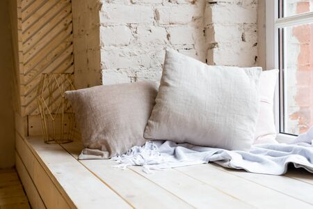 cozy still life, warm woolen knitting decoration on windowsill against brick wall and window.boho style in living room interior with elegant pillows. loft apartment. Home decor on windowsill. Фото со стока