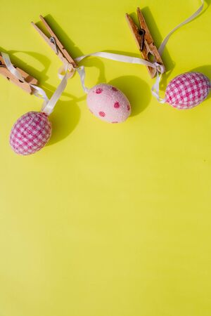 Happy Easter.Greeting card with easter eggs hanging on clothesline, yellow bright background.invitation card with colorful easter eggs. Copy space