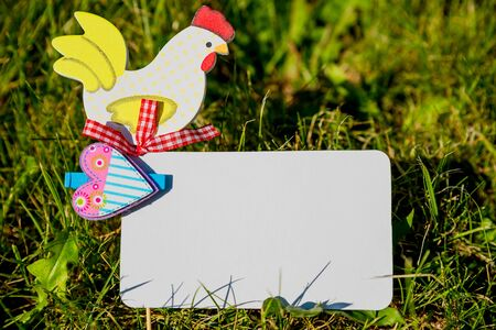 Mockup white greeting card and easter eggs on green grass background.Easter holiday concept with copy space.Easter background with traditional symbols like spring hare and eggs symbolising egg hunt.