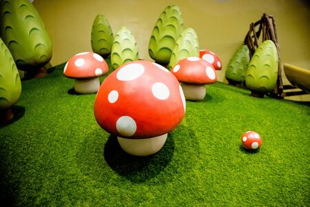 Decorative fly agaric on a green lawn.red mushrooms decoration.many mushrooms, big toys ,ornament.Fairy forest with magic mushroom. Plastic decoration on the lawn.Kids playground.