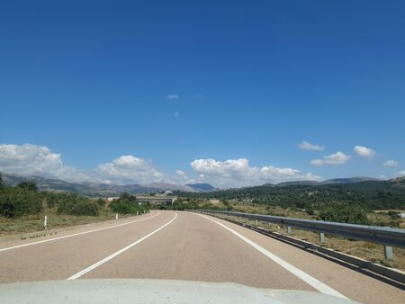 View of an empty mountains road.right-hand traffic. moving car. Travel with car in europe.beautiful hill landscape through windscreen in sunny day. Driving a car on mountain winding road. Spain,Italy Speedway.