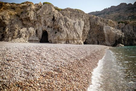 famous rocky beach of Traganou with iconic caves, Rhodes island, Dodecanese, Greece.view of the beautiful stones beach on the east coast of the island of Rhodes, Greece.Selective focus.