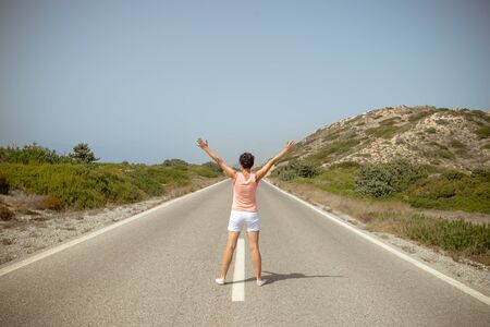 welcome to nature. Happy Young woman Young female with hands raised standing on asphalt road near forest Фото со стока