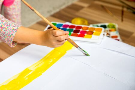 Preschool children, little girl painting and drawing.Child painting in the kindergarten.Child holding a paintbrush and working on a painting for art class.art school, creativity and people concept Фото со стока