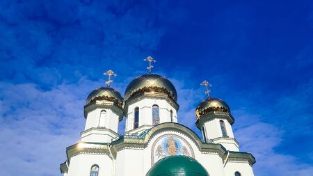 White orthodox church against the blue sky.Three domes with crosses. Golden domes of the church , ancient Christian monastery.Eastern orthodox crosses on gold domes againts blue sky with clouds