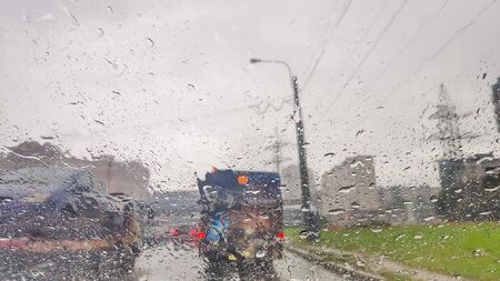 Background is blurred, raindrops on the windscreen to car. Water droplets on the glass surface on the road. Blur, bokeh and street lights behind.heavy rainy and slippery road. Abstract bad weather car on the highway.
