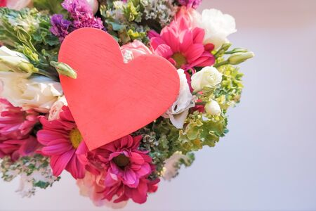 Valentines day elegant bouquet with roses flowers, Lisianthus, chrysanthemum and red wooden heart, sign of love.