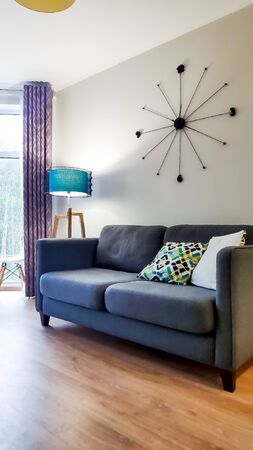 Beautiful modern living room with blue sofa and floor lamp