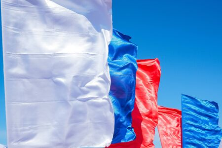 Three colorful flags on flagpoles against blue sky with perspective, corporate flag ,symbol, copy space. Banque d'images