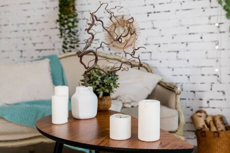 white candles on wooden coffee table in cozy living room interior Stock Photo