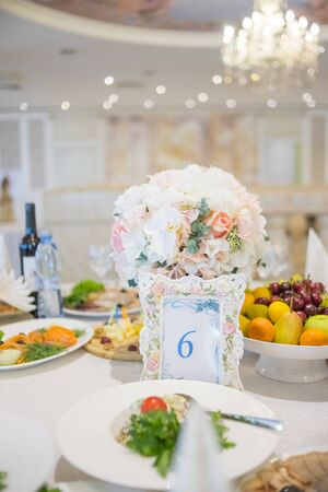 Set a festive wedding table with number six with white cloth full of food, luxury red bouquets, refreshment, plates and glasses.Table number 6 printed on white card.snacks, fruits plates. Happy birthday party 免版税图像