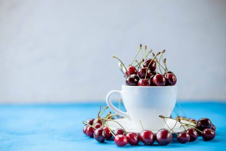 Bright juicy red berries and leaves. Sweet cherry in ceramic cup. Close-up, selective focus image. Healthy concept. Red ripe cherries. natural fresh vegetarian food.Copy space