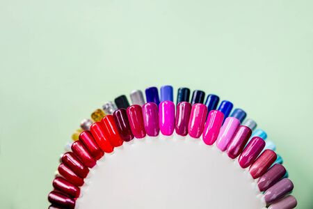 Background of multicolored nail polish samples. Top view of the color palette of nail services in beauty salon. Fashion manicure. Gel lacquer. Selective focus. Copy space.