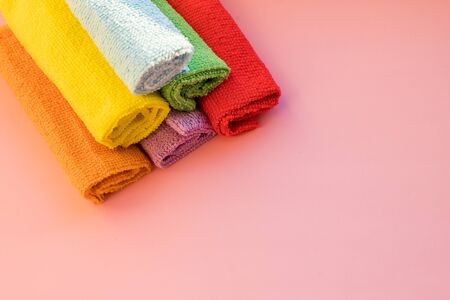 stacked colorful microfiber cleaning cloths on a pink background. Colorful, dry microfiber cloths for different surfaces cleaning in kitchen, bathroom ,other rooms. Copy space for text or logo.