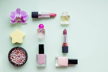 Colorful make up products with golden pursue close up pop art flat lay scene