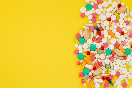 doctors office with colorful pills on yellow background.protection. Dangerous virus. Virus epidemic concept.Tablets,Medicine and healthy. Close up of capsules. Differend kind of pills.Copy space