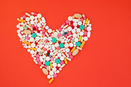 Danger for heart, medication,many colorful pills, capsules on red background.Diet and healthy lifestyle.Obesity leads to strokes, heart attacks,shortness of breath,psychological problems,adaptation in society