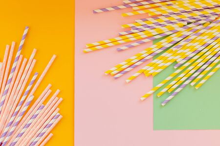 Drinking paper straws on yellow background with copy space. Top view of colored paper disposable eco-friendly straws for summer cocktails. Stock Photo
