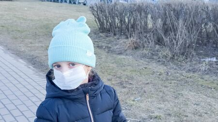 Little kid the child is wearing a coat and hat, on the street. Face mask for protection coronavirus outbreak. New coronavirus 2019-nCoV . Facial hygienic mask for Safety ,virus and flu outdoor. Standard-Bild