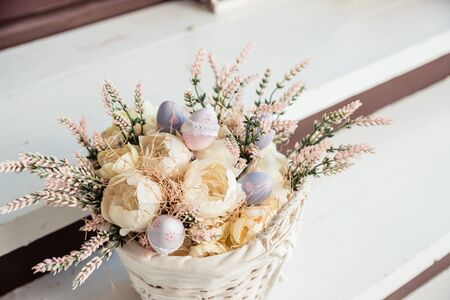 Festive Easter decoration, dry plants, flowers in a basket on wooden table. spring flowers, handmade present for the holiday, Easter Holiday.Easter greeting card