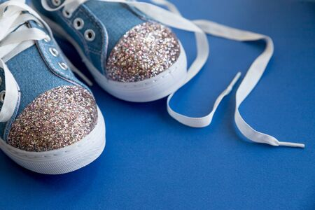 Denim children's shoes with laces on a wooden background.Kid's fashion