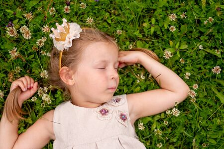 Sweet little girl sleeping on a green grass. girl lying on the grass. child relaxating outdoor.Cute girl lies on her back on the green grass lawn in near country house, relaxing and meditating in nature Standard-Bild