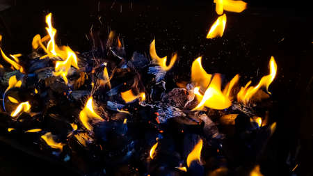 Hot coals in the fire.actively smoldering embers of fire.Burning firewood in the fireplace close up, BBQ fire.black burned charcoal Stock Photo