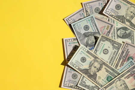 Scattered 100 American Dollars.Economic Crisis dollars money cash on yellow background. Background is banknote of US Dollar.many identical money notes in a mess.Copy space