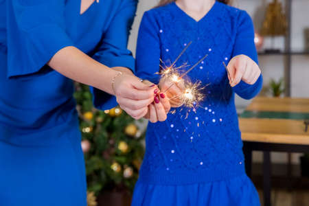 sparkler in hands over Christmas background. family celebrate Christmas time together, focus at sparkler,bengal fire.mother and daughter in blue dresses holding sparklers. Happy family concept