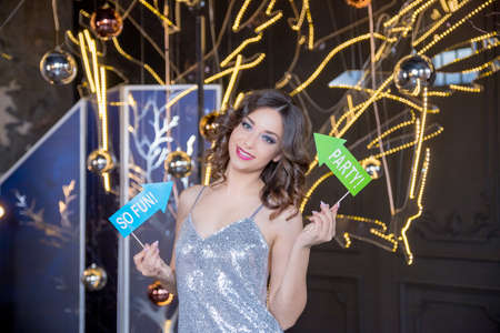 Young girl is preparing for Birthday,christmas or new year party with photo booth props. lady in silver shiny dress is holding party signs, arrows on stick.corporate, celebration and holidays concept Stock Photo
