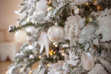 Christmas decoration with fir branch,silver Christmas ball and gift box.Beautiful green Christmas tree decorated with silver and white balls and garlands.Festive background.