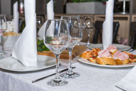 Served for a banquet table. Wine glasses with napkins, glasses and salads.