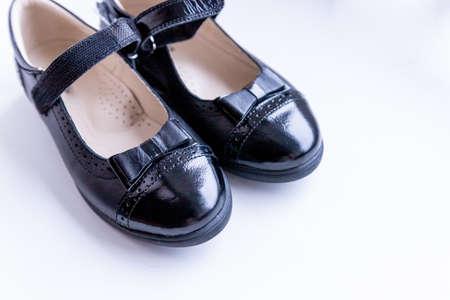 Fashionable black stylish girls leather loafers on white background. Fashionable school shoes.Elegant kids shoes Foto de archivo