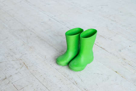 Childrens boots.Pair of children green rubber boots, gumboots for rainy days.Fall, Autumn or spring concept - kids shoes. Copy space